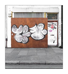 Graffiti (Time), East London, England. (Joseph O'Malley64) Tags: time graffitiartist graffiti urbanart publicart freeart eastlondon eastend london england uk britain british greatbritain closedforbusiness formerbusinesspremises plywoodpanels woodenpanels shutter rollershutter door doorway woodendoor window burglaralarm shop shopfront sign signage junctionbox wiring electricalwiring stencil tags throwie drainpipe stopcock pavement granitekerbing tarmac singleyellowline parkingrestrictions urban urbanlandscape aerosol cans spray paint x100t fujix100t fujix accuracyprecision