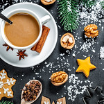 A cup of coffee with gingerbread and winter spices on the background with snow and Christmas tree branches. Winter mood thumbnail