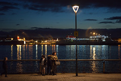 Couple by the Mersey at Night (Tony Worrall) Tags: night evening liverpool dark lit lights neon docks scene scenic merseyside scouse city welovethenorth nw northwest update place location uk england north visit area attraction open stream tour country item greatbritain britain english british gb capture buy stock sell sale outside outdoors caught photo shoot shot picture captured ilobsterit instragram couple mersey candid lamp