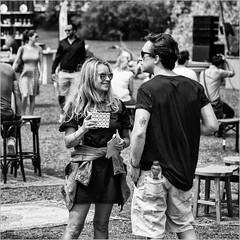 Plenty of tokens left (John Riper) Tags: johnriper street photography straatfotografie rotterdam park kannenkruiken kannen kruiken square bw black white zwartwit mono monochrome netherlands candid john riper canon 6d 24105 l sun glasses mirror smile boy girl tattoo lily drink tokens crowd fun bottle water blond goldy locks smartphone