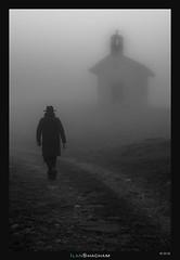 Take me to church (Ilan Shacham) Tags: landscape street dark man chapel fog mist vertical atmosphere fineart fineartphotography cervinia italy hat bw blackandwhite path walk silhouette