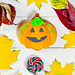 Halloween gingerbread pumpkin with autumn leaves and candy