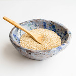 Uncooked white quinoa in a ceramic bowl on isolated on white background thumbnail