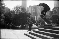 Skaters Doing Jumps (Mark Klotz) Tags: hc110 homedeveloped pulledfilm rangefindercamera petri7greenomatic petri7 street streetphotography ishootfilm analog blackandwhitefilm kodaktrix400 film markklotz vancity 604now robsonsquare skateboard vancouverartgallery vancouver sweetjumps skateboardtricks jumps skateordie sk8ordie skateboarding