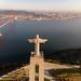 Luftaufnahme von hinten der Cristo Rei Statue über dem Tajo auf Lissabon blickend, mit Ponte 25 de Abril Brücke