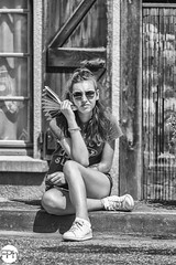 Looking bored (Frankhuizen Photography) Tags: tourdefrance audressein pyrénées sun glasses girl meisje vrouw woman france 2018 street straat fotografie photography people frankrijk black white zwart wit candid tour étape 16 pyreneeen pyrenees zonnebril monochrome sit fashionable hair pretty brunette