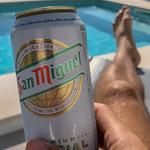 Eine Dose San Miguel Bier in der Hand eines Mannes der an einem Pool auf Mallorca entspannt thumbnail