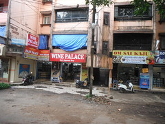 Drab and Dowdy (RubyGoes) Tags: calangute goa india shops liquor caju blue tarpaulin apartments mangotree green leaves road plasticchairs balconies winepalace white red yellow bardez omsai governmentapproved weeds men window pane
