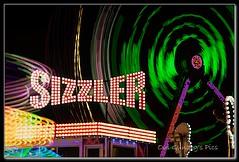 Sizzler (Oul Gundog) Tags: ulster newtownards co down northern ireland united kingdom fair ground lights ride spin machine sign building blur