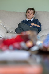 Dan being lazy (iamthecandleman) Tags: a7r 85mm zeiss sony telivision tv watching uniform school child nephew niece portrait people photo forground background
