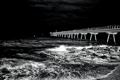 Rocking... in black (Fnikos) Tags: sea water waterfront mar mare wave seascape landscape pont puente pier bridge people architecture construction rock sand coast beach shore seashore bay night noche nit sky skyline light nightview nightshot blackandwhite monochrome outdoor