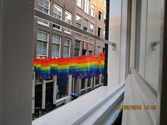 Warmoesstraat (RubyGoes) Tags: bunting rainbow amsterdam netherlands hillstreetblues window windows wheeliebin yellow bike bricks wall red orange green violet pane