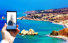 High contrast vibrant image of famous blue emerald sea bay near the birthplace of Aphrodite of Cyprus in summer 2018 with human hand and smart phone displaying boats (ABglavin) Tags: aerial aphrodite attraction bay beach beautiful birthplace blue coast cyprus europe famous highcontrast island landscape mediterranean nature outdoors relaxing rock sea seascape seaside shore splash stone summer sunny tourism travel vacation vibrant view water wave collage smartphone humanhand composite computer image yachts boat nautic vessel transportation trail reflection