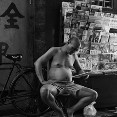 """""""night reading"""" (i) (hugo poon - one day in my life) Tags: nikonfe2 nikon50mm18 film kodak tmax400 citynight hongkong northpoint northpointroad bicycle reading longnight solitude store vanishing reminiscing newsstand"""