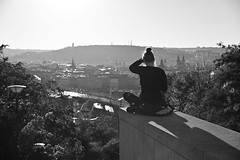 Girl enjoying evening view from square by the Vitkov monument (Pavel's Snapshots) Tags: sunday leisure listeningmusic retro vintage sunny distant evening bw sunset lovely romantic girl prague praha czech czechrepublic woman bright sunlight light urban view panorama aerial hill autumn blackandwhite nikon d750 city town historic historical monochrome sitting music headphones streetphotography vitkov 70mm enjoying relaxing