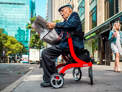 The New Yorkers - Rolling News (François Escriva) Tags: street streephotography us usa nyc ny new york candid olympus omd old man elder blue green red colors hat newspapers wheelchair sun light photo rue sky towers scooter