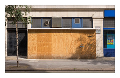 The Built Environment, West London, England. (Joseph O'Malley64) Tags: thebuiltenvironment newtopography newtopographics building structure urban urbanlandscape architecture architecturalphotography britishdocumentaryphotography documentary westlondon london uk britain british england greatbritain renovation construction alteration plywoodpanels woodenboards worksite buildings structures 20thcenturybuilding stonecladding stonework windows leadedwindows frostedglass woodendoors woodenpanelleddoors padlocks padlocked straphinges louvres extractorfan signs signage tree silverbirchtree doors entrances exits shadows concrete accesscover tarmac granitekerbing singleyelowline parkingrestrictions fujix fujix100t accuracyprecision