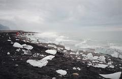 slivers of icebergs at the edge of the sea (manyfires) Tags: iceland travel europe vacation shore shoreline sand sunset moody bokeh nikonf100 35mm analog film southerniceland southiceland ocean atlanticocean jokulsarlon vatnajökullnationalpark jokulsarlonglaciallagoon glaciallagoon glacier glacial ice icebergs iceberg landscape sea