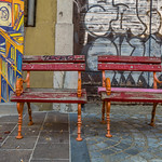 Two small benches near mural on the wall thumbnail