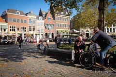 Gouda square (PaulHoo) Tags: fujifilm x70 gouda city candid people citylife 2018 sun square bench talk conversation bicycle streetphotography