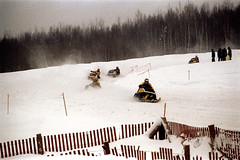 50-355 (ndpa / s. lundeen, archivist) Tags: nick dewolf nickdewolf color photographbynickdewolf 1973 1970s film 35mm 50 reel50 winter maine centralmaine snow snowy snowmobile snowmachine race snowmobilerace racing course fence snowmobiles snowmachines racecourse finishline ussa racer driver helmet people onlookers spectators helmets drivers racers skidoo trip wintertrip vacation snowfence