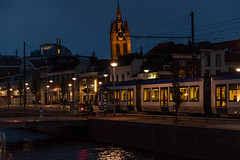 Tram passing by with the tower of the 'Oude Kerk' (dvdkolk) Tags: delft netherlands church tower canal tram dusk evening