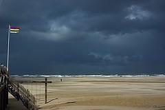 Dark clouds over the beach (Greet N.) Tags: terschelling island beach darkclouds sand water waddensea rain wind flag