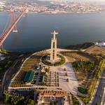 Luftaufnahme der Cristo Rei Statue von hinten mit Ponte 25 de abril Brücke thumbnail