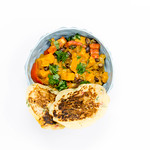 Hello Fresh - Carribian Sweet Potato Coconut Stew with Black Beans and Tasty Bananapancakes in blue bowl on white background - Top view thumbnail