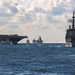 USS Ronald Reagan, left, steams alongside USS Chancellorsville during a pass in review