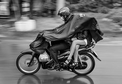 Faith & Vanity - 2012 (Austin Westervelt) Tags: vietnam transportation road street bw blackwhite blackandwhite monochrome people person moped rain wet reflection movement motion