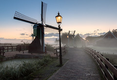 On a misty morning (rudi.verschoren) Tags: mill morning mist mood holland heritage outdoor old overlooking lamp post walkway walkpath water autumn landscape sunrise colors contrast zaanse schans europe exposure canon