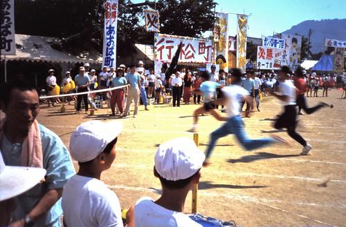 adult sprinting event, kids look on