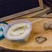 Noa - Hummus-Brotaufstrich mit 30 Prozent weniger Fett auf einer Holzplatte mit Brot