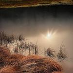 Die Sonne spiegelt sich im dunklen Karsee, Reif liegt über dem Gras. thumbnail