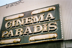 Paradis - Analog - From moving Vehicle (Irrational Photography) Tags: retro vintage antique hipster old analogue analog picture photo film grain noise slr 35mm 120 35 montreal quebec city canada point shoot ultramax gold kodak pushed zoom 70 cinéma cinema movie paradis paradise street walk walking photography candid path people shop shoppe window wall road abandoned abandon close closed sign graffiti