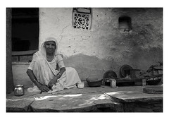 at home in the shade (handheld-films) Tags: india portrait portraiture woman women people individual elderly cooking utensils kitchen outdoor indian rural rajasthan dappledlight blackandwhite mono