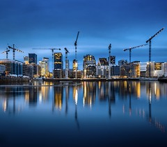 Business as Usual (b.adolphi) Tags: oslo norway bjørvika blue bluehour buildings cranes construction water sky yellow sunset skyline city
