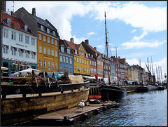 Copenhagen waterway. (Country Girl 76) Tags: copenhagen denmark waterway boats water architecture landing stage hopping bird buildings coloured frontage sky clouds city ripples masts