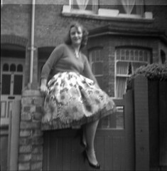 Girl sitting on a gate (vintage ladies) Tags: blackandwhite vintage people photograph 60s female woman lady 60slady 60swoman 60sstyle smile smiling cardigan skirt sitting gate blurred house portrait eoshe