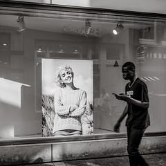 passing by (Gerard Koopen) Tags: nederland netherlands amsterdam capital city reflections man straat street straatfotografie streetphotography streetlife walking mobile bw blackandwhite blackandwhiteonly fuji fujifilm x100t fashion poster woman smiling smile laughing 2018 gerard koopen gerardkoopenphotography