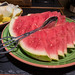 Slices of watermelon o a plate with tongs for serving