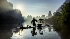 On the Water (Dan_Fr) Tags: guilin xingping guangxi yangshuo li river cormorant fisherman birds boat tradition custom dawn sunrise travel landscape mountain hill karst scenery china asia water reflection sky sun sunstar beautiful amazing tree person lamp splash bamboo raft sony a7r