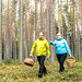 man and a woman walking in forest in autumn