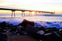 Sunrise behind rocks (Fnikos) Tags: sea water mar mare wave landscape seascape coast beach bay shore seashore sand dark light bridge puente pont pier sun sunrise cloud architecture construction rock sky skyline outdoor