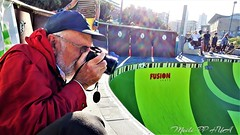 486. Up Close At The Rink (Meili-PP Hua 2) Tags: man photographer guy red rink skateboarding skateboardingrink men skateboarders yellow green bright sunny sports spectators action streetphotography snap shutterbug camera lens cap