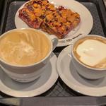 Milchkaffee und Cappuccino mit Pflaumen-Streuselkuchen auf einem Tablet in der Nahaufnahme thumbnail