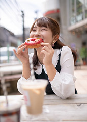Young woman eating doughnut in city (Apricot Cafe) Tags: ap2a0286 asia asianandindianethnicities japan japaneseethnicity shibuyaward tokyojapan autumn bench capitalcities carefree casualclothing chaitea charming colorimage day doughnut eating enjoyment foodanddrink happiness harajukudistrict icecoffee leisureactivity lifestyles oneperson oneyoungwomanonly outdoors people photography realpeople sitting smiling street student sustainablelifestyle table universitystudent waistup women youngadult