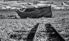 The end of the line (David Feuerhelm) Tags: momochrome nikkor bw blackandwhite schwarzundweiss noiretblanc negroyblanco contrast beach shingle kent england boat rails abandoned sky clouds nikon d750 2470mmf28 dungeness coast shore