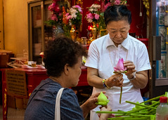 Preparing offerings (Goran Bangkok) Tags: bangkok thailand temple religion buddhism chinese offering woman flower lotus bud